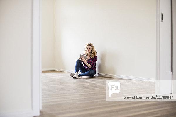 Junge Frau im neuen Zuhause sitzt auf dem Boden mit Tablette