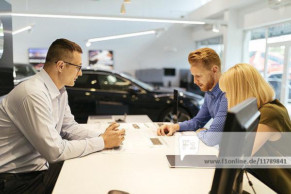 Verkäufer berät Ehepaar im Autohaus