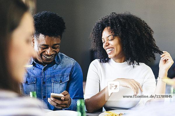 Ein glückliches Paar teilt sich sein Handy am Esstisch.