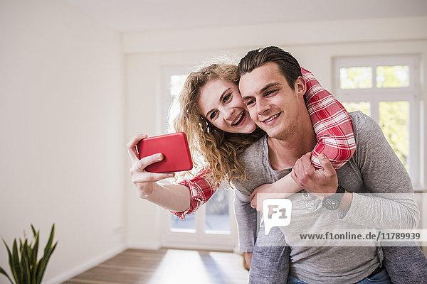 Glückliches junges Paar in neuem Zuhause mit einem Selfie