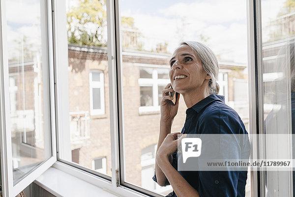 Geschäftsfrau am Telefon am Fenster