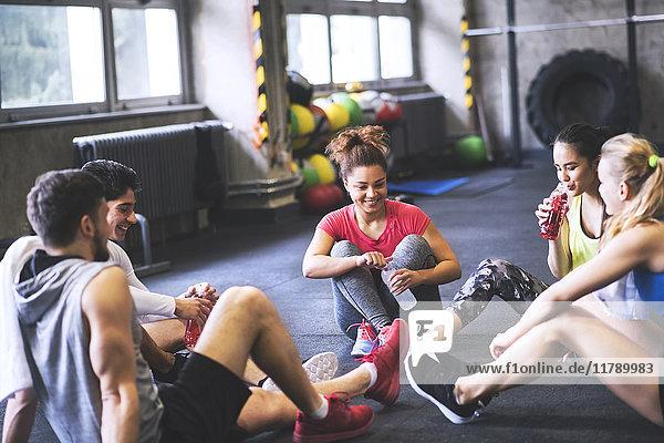 Gruppe junger Leute bei einer Pause im Fitnessstudio