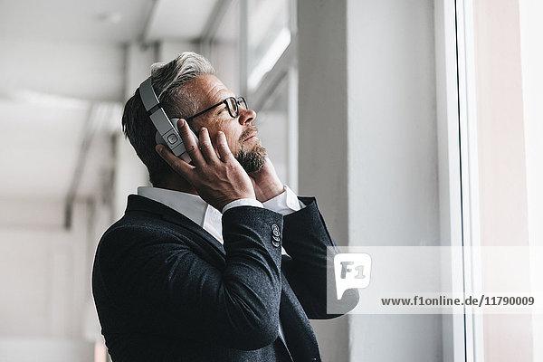 Businessman wearing head phones   listening music
