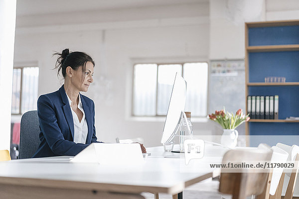 Geschäftsfrau arbeitet am Schreibtisch in einem Loft