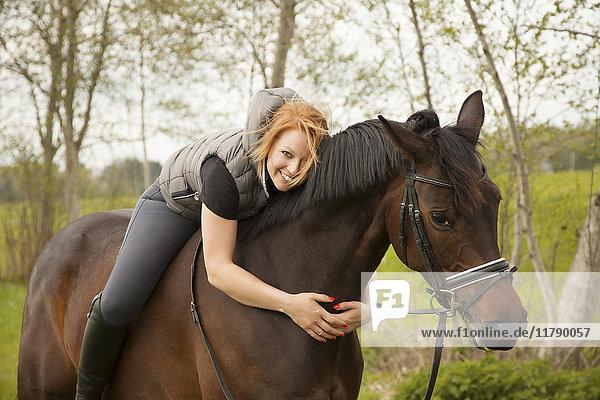 Lächelnde junge Frau auf einem Pferd