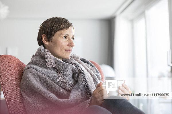 Porträt einer Frau  die sich bei einer Tasse Kaffee zu Hause entspannen möchte.