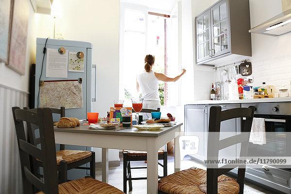 Rückansicht der Frau beim Öffnen des Küchenfensters am Morgen