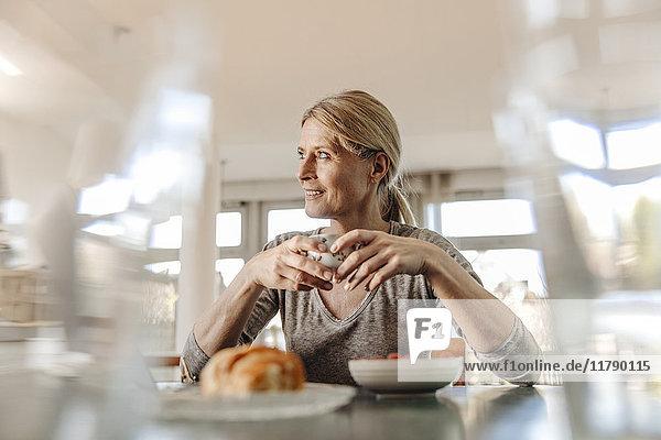 Frau zu Hause beim Frühstücken am Tisch sitzend