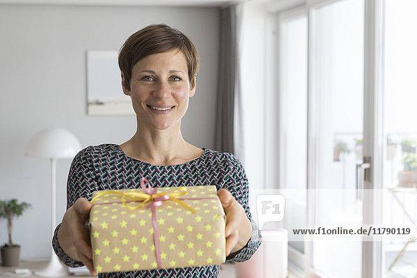 Porträt einer lächelnden Frau mit Geschenk