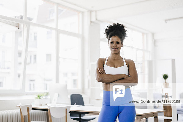 Fitte junge Frau steht in ihrem Home-Office