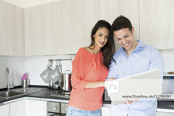 Smiling couple with laptop in kitchen