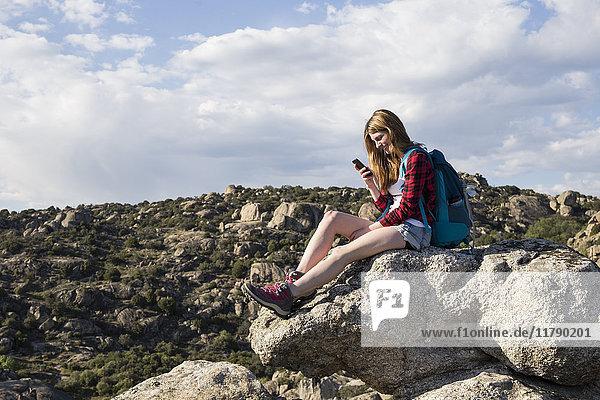 Spanien  Madrid  junge Frau  die sich während eines Trekking-Tages auf einem Felsen ausruht.