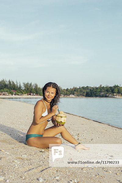 Lächelnde Frau am Strand sitzend mit Getränk