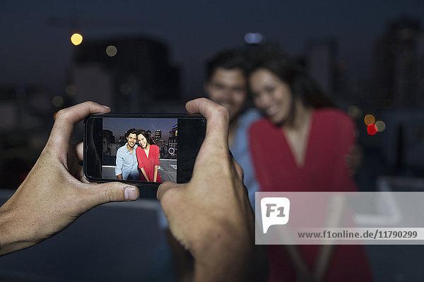 Junger Mann beim Fotografieren eines Paares auf einer Dachparty