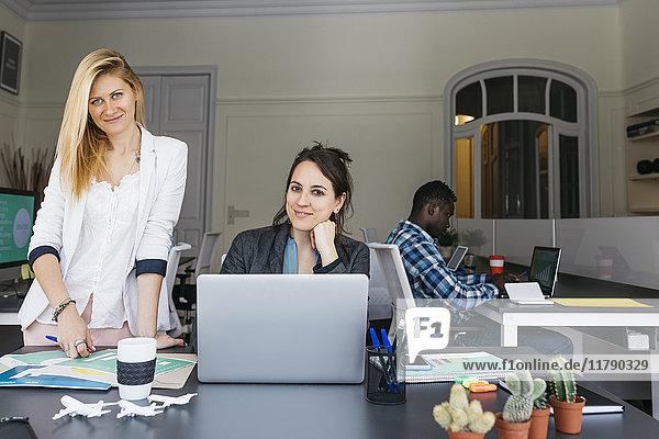 Junge Geschäftsfrauen arbeiten zusammen  mit dem Laptop  Kollegin sitzt im Hintergrund