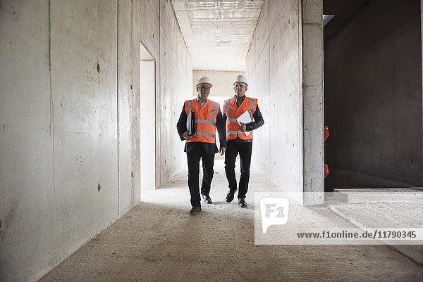 Zwei Männer  die in einem Gebäude im Bau sind.