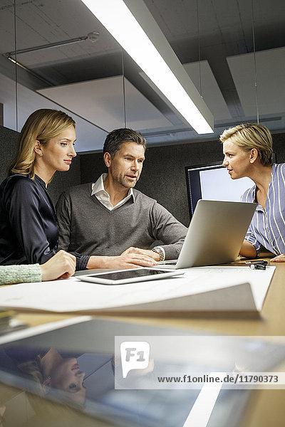 Kollegen mit Laptop  die eine Besprechung in der Besprechungsbox haben