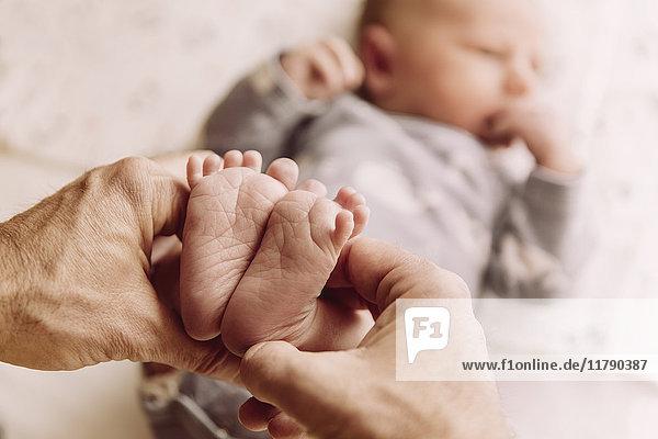 Füße des neugeborenen Jungen werden von Vaters Händen gehalten.