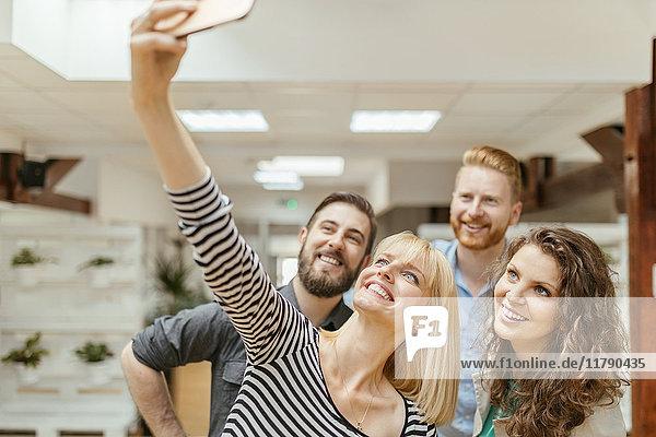 Kollegen  die einen Selfie mit Smartpone nehmen