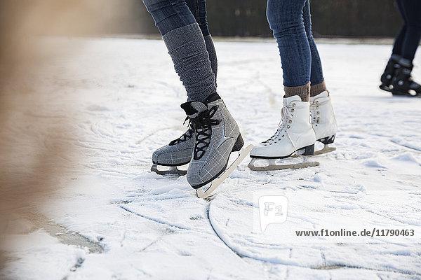 Füße von Schlittschuhläufern auf dem zugefrorenen See