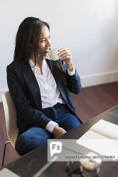 Lächelnde Geschäftsfrau beim Kaffeetrinken während eines Meetings im Büro