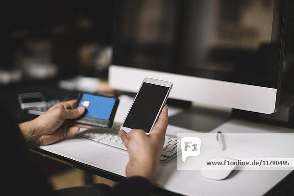 Männerhand mit Smartphone und Kreditkarte am Schreibtisch  Teilansicht