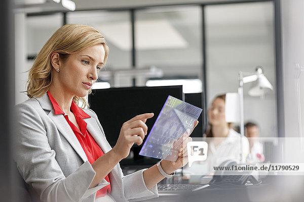Geschäftsfrau am Schreibtisch im Büro mit futuristischem Tablett
