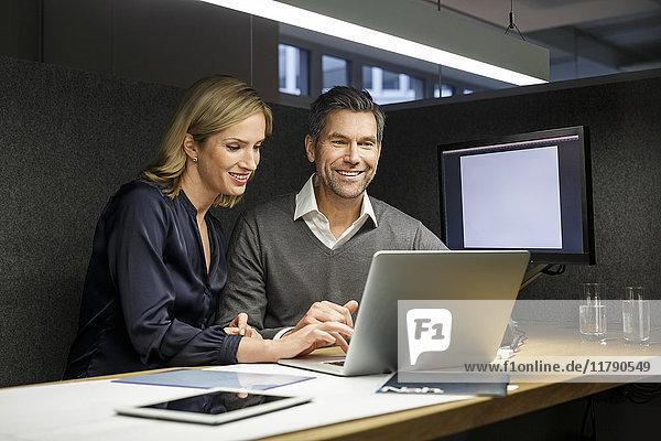 Geschäftsfrau und Geschäftsmann mit Laptop in Besprechungsbox