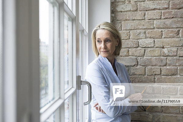 Mature businesswoman standing at window  looking worried