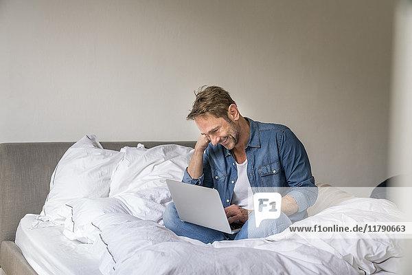 Lächelnder reifer Mann auf seinem Bett sitzend mit Laptop