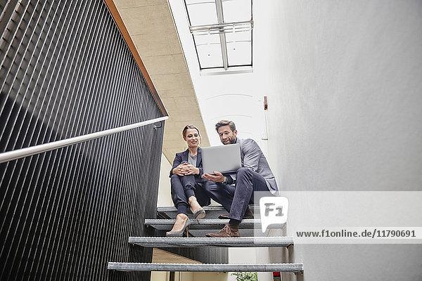 Geschäftsmann und Geschäftsfrau sitzen auf einer Treppe im Büro und teilen sich einen Laptop.