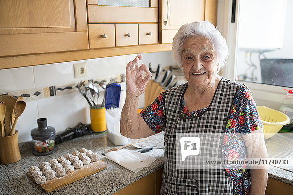 Porträt einer lächelnden Seniorin mit ok-Zeichen in der Küche
