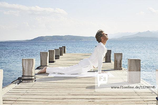 Reifer Mann bei Yoga-Übungen am Steg