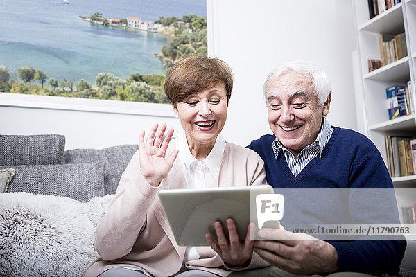 Seniorenpaar sitzt auf der Couch und macht einen Videoanruf auf ihrem digitalen Tablett.