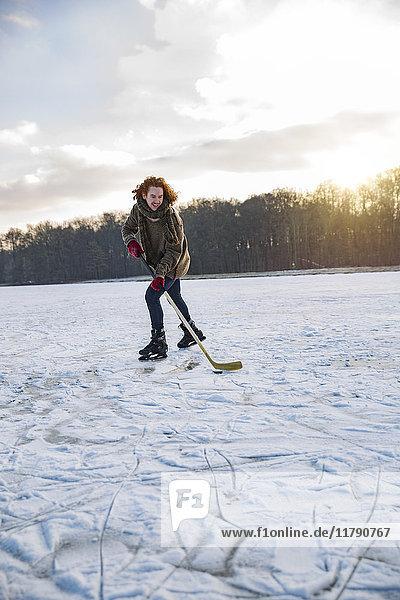 Mann spielt Eishockey auf gefrorenem See