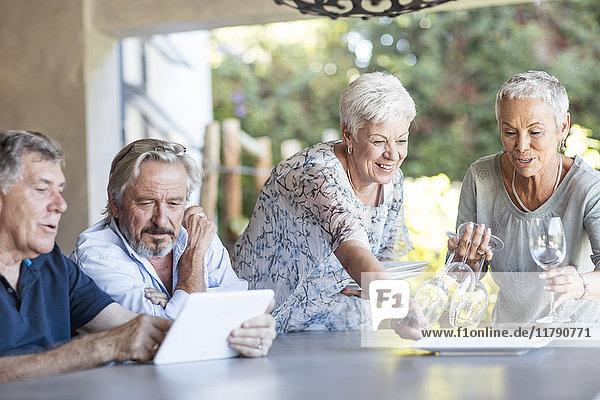 Zwei ältere Frauen decken den Tisch auf der Terrasse  während ihr Mann die Tablette benutzt.