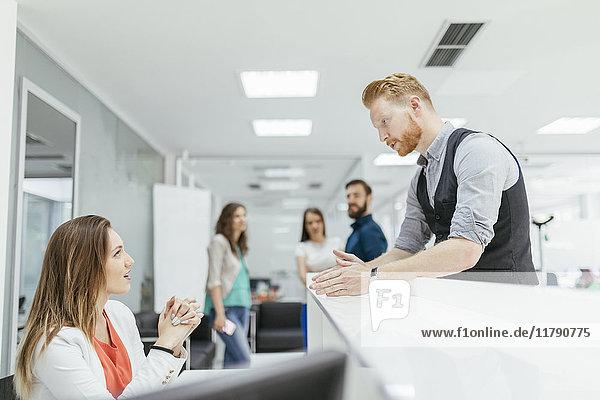 Geschäftsmann und Frau diskutieren im Büro  Kollegen schauen zu