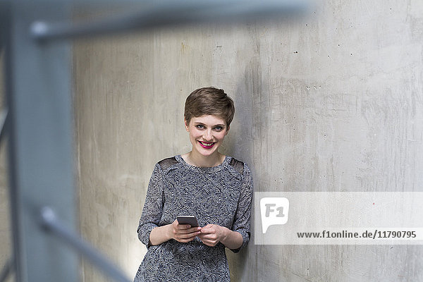 Portrait of smiling woman holding cell phone at concrete wall