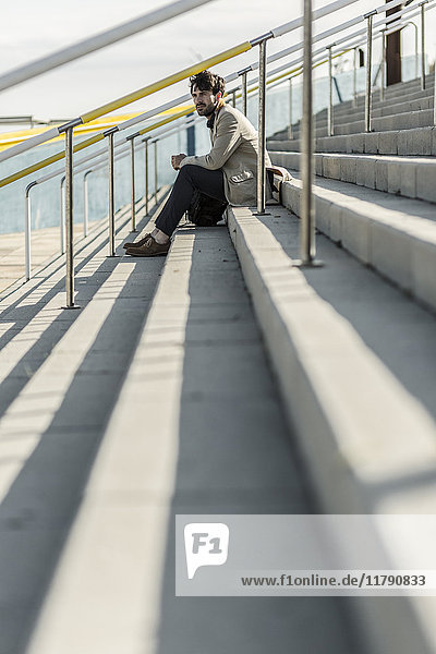 Pensive man sitting on steps outdoors