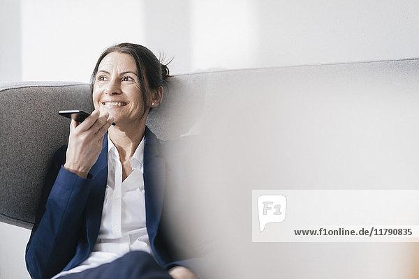 Porträt einer lächelnden Geschäftsfrau auf der Couch mit dem Handy