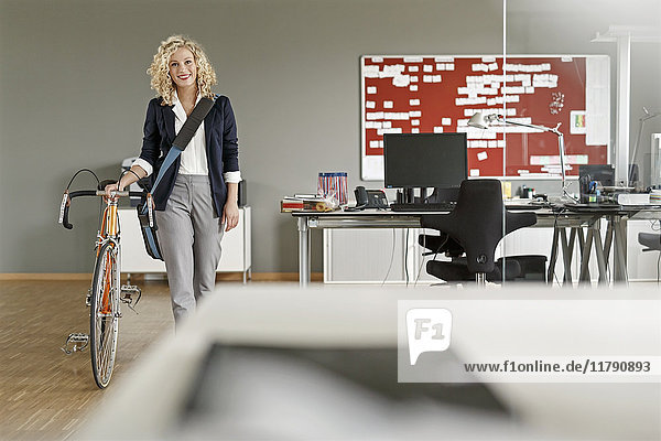 Lächelnde Frau mit Fahrrad im Büro
