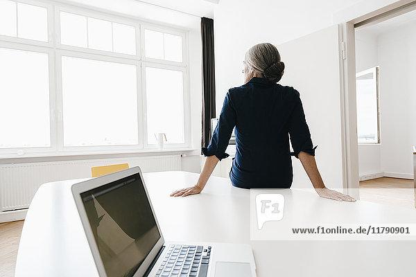 Geschäftsfrau sitzt auf dem Tisch im modernen Büro