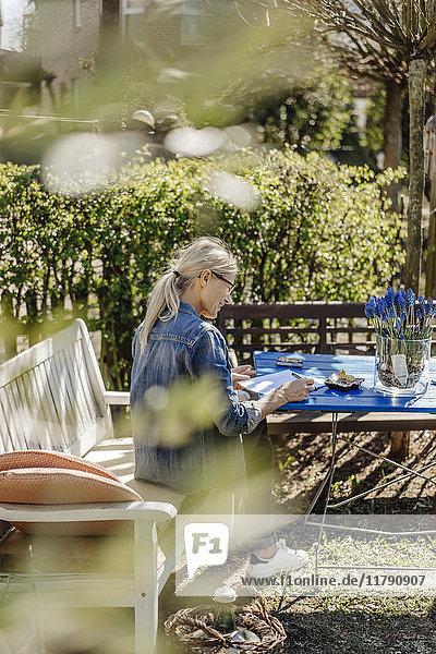 Frau schreibt einen Brief auf der Gartenbank