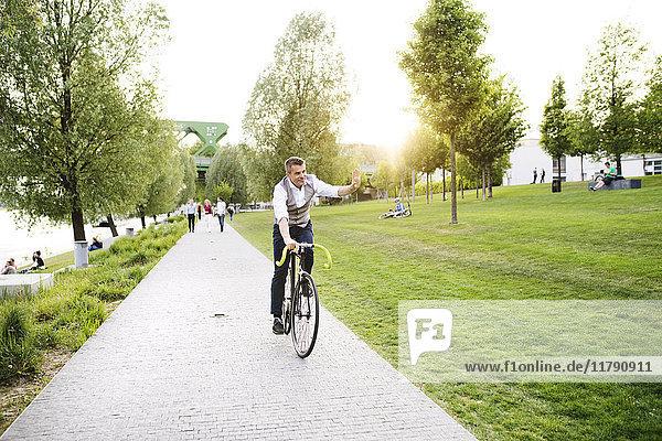 Selbstbewusster  reifer Geschäftsmann auf dem Fahrrad an der Uferpromenade