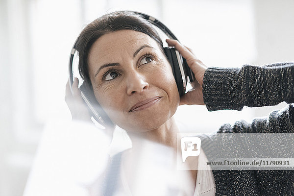 Portrait of smiling woman listening music with headphones