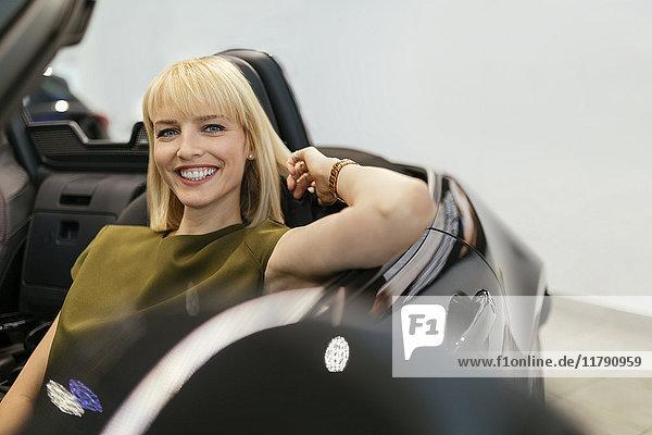 Blonde Frau sitzend im Cabrio im Autohaus