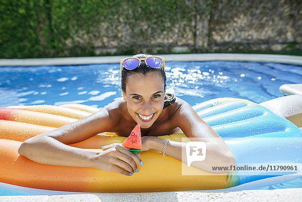 Porträt der glücklichen jungen Frau auf Luftmatratze im Schwimmbad
