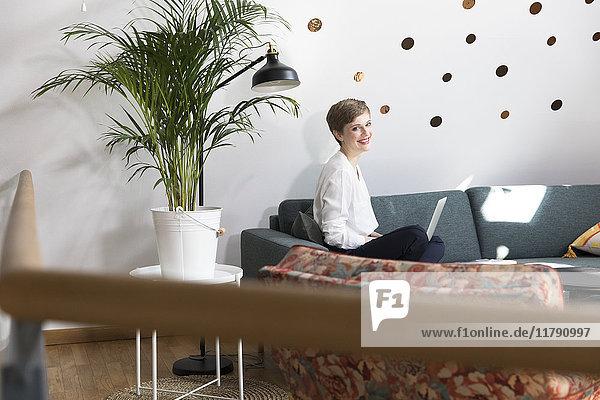 Frau mit Laptop auf der Couch im modernen Büro
