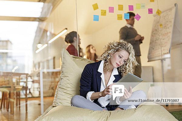 Frau im Büro mit Tablette im Bohnenbeutel mit Besprechung im Hintergrund