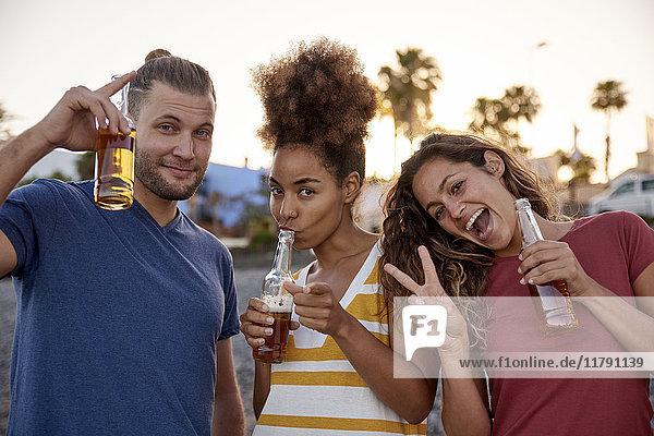 Porträt von drei Freunden mit Bierflaschen  die sich am Strand amüsieren